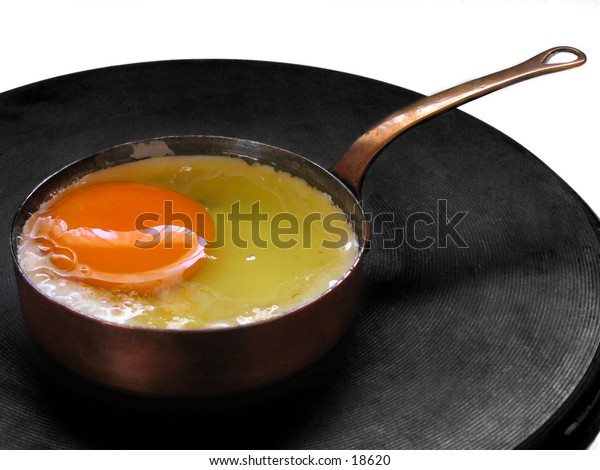An egg being fried in a miniature copper frying pan.