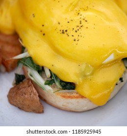 Egg benedict or egg florentine on white plate. Melted cheese sauce over poached egg and spinach on muffin. Breakfast background