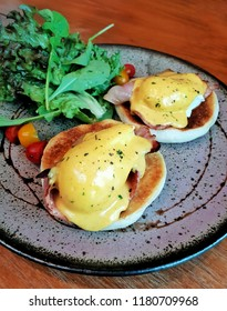 Egg Benedict, hollandaise sauce and bacon with green lettuce and rocket vinaigrette dressing salad on ceramic plate