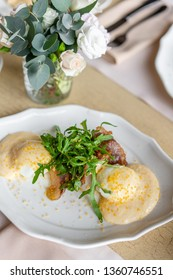 Egg Benedict with little salad on the plate with bacon and arugula. Two eggs delicious hollandaise sauce. Light morning Breakfast on table in restaurant.