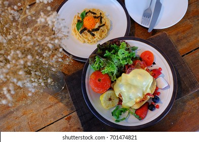 Egg Benedict with little salad on the wooden plate and Ebiko Pasta on white plate in the breakfast