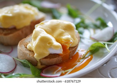 Egg Benedict - Poached egg on toasted English muffin with fresh hollandaise sauce, Delicious homemade breakfast, Poached egg with flowing out yolk.