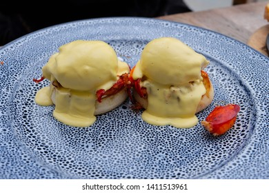 Egg Benedict with smoked bacon topped with hollandaise sauce delicious breakfast served on a beautiful plate.