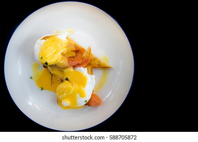 Egg Benedict with smoked salmon and fresh Hollandaise sauce on black background