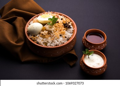 Egg Biryani - Basmati rice cooked with masala roasted eggs and spices and served with yogurt, selective focus