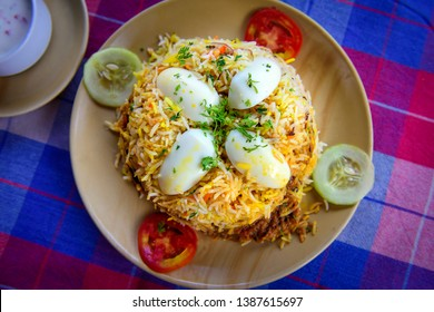 Egg Biryani - Basmati rice cooked with masala, eggs and spices, overhead view, close up. Egg Pilaf or Pulao served with vegetables and yogurt.