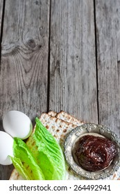 Egg, bitter salad leaves, matzot and haroset - traditional jewish passover celebration elements. Copy space background.