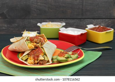 Egg burritos wtih eggs, chorizo, avocado, cheese and salsa.  Rustic wooden table and wall, condiments on the side.