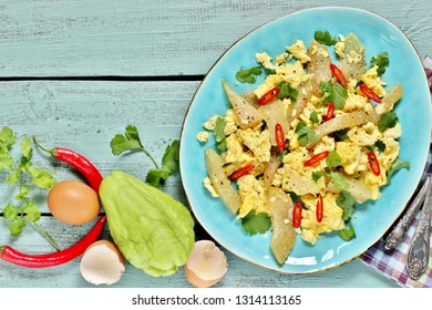 egg chayote in mexican style. whipped eggs are fried with chopped chayote with cilantro and spicy chili. recipe with chayote. top view. Mexican food. copy space. place for text. top view.
