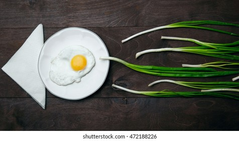 Egg , chives (green onio) and white plate look like sperm competition, Spermatozoons floating to ovule.Wooden background.Napkin like arrow.Horizontal shot