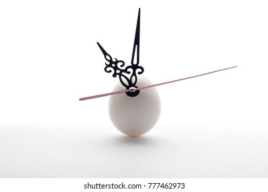 egg and clock hands on white background