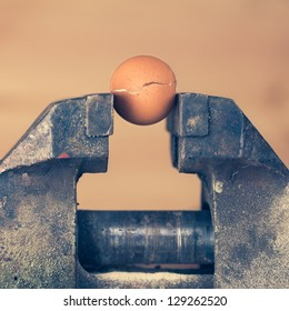 Egg Is Cracking under the Pressure of Vice (color toned Image)