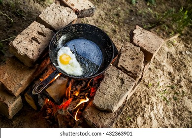 the egg is fried in a cast iron black skillet on fire