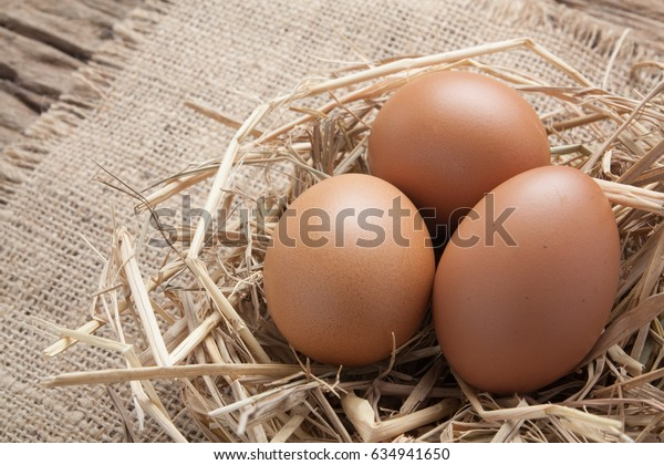 egg in hay nest on old wooden table background