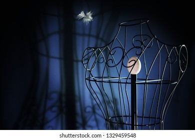 egg in a metal tailor doll like in a bird cage and a flying feather, surreal art concept for longing and loneliness, dark blue background with copy space, selected focus