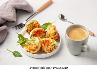 Egg muffins ( bites) with vegetables and spinach leaves  in a plate on a gray background