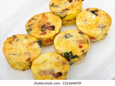 Egg muffins with spinach, bacon, cheese and tomatoes on white plate