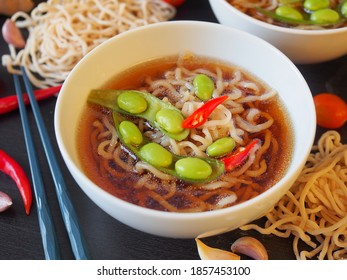 Egg noodle or ramen with soysauce soup topping with green pea and red chili pepper in a white color bowl, Asian food.