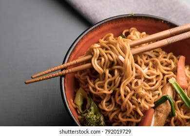 Egg noodle with vegetable and chicken in a black-orange bowl with soy sauce
