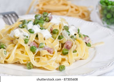 Egg noodles with cream, ham and green peas
