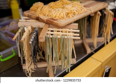 Egg noodles of different colors on a wooden board. Row of three small different colored bundles of wheat ribbon pasta strips on wood grain table background. street food.