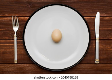 Egg on plate with knife and fork on table top