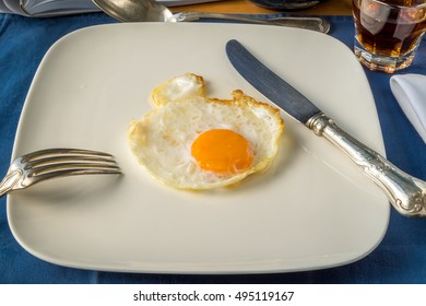 Egg on white plate with elegant fork and knife