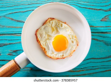 Egg over easy on white pan and wooden board