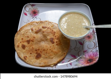 Egg Paratha with Dalia or Daliya, Cereal Food Know as Bulgur Cooked in Milk Served with Egg Stuffed Paratha or Indian Stuffed Bread with Egg or Fried Flatbread, Selective focus.