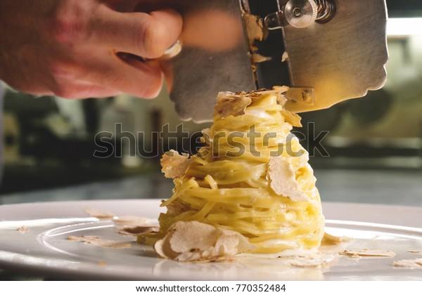 Nudelgerichte aus Eiern, typisch italienisch, mit feinem weißem Trüffelgras. Konzept: Gourmetküche, Trüffeln, italienische Nudeln, feine Gerichte.