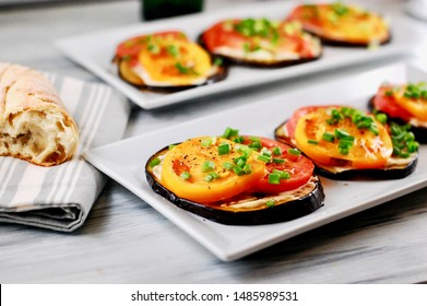 Egg plant appetizer with tomato on a plate, healthy appetizer, veggie appetizer, round egg plant for lunch or dinner, Italian appetizer