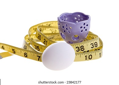 An egg and purple eggcup with a yellow tape measure.  Conceptual image for dieting, weight loss, etc.