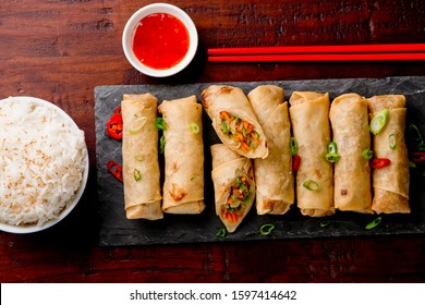 Egg rolls or spring rolls fried.Traditional Chinese Thai restaurant appetizer, spring rolls or egg rolls. Made from wonton wrappers and filled with Chinese veggies and served w/ chili dipping sauce.