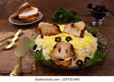 Egg salad with cheese and crab meat, toasted toast, basil  leaves, pickled olives, the image of the pig's head – the symbol of 2019.
