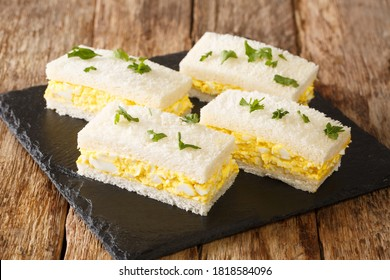 Egg salad tucked between slices of white bread, Japanese egg sandwich Tamago Sando close-up on a slate board on the table. Horizontal