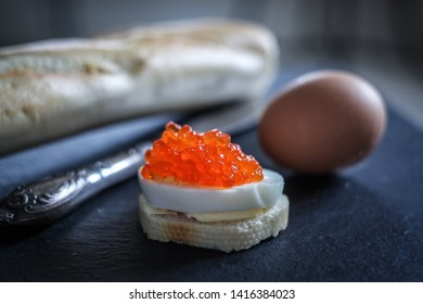 Egg sandwich with red caviar on a black stone board with wheat bread and vintage knife. It can be used for food and cooking magazines; healthy lifestyle books; for interior and print design.