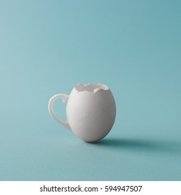 Egg shell coffee cup on pastel blue background. Minimal Easter concept.