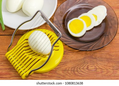 Egg slicer with egg in it closeup, boiled whole peeled and partly sliced eggs in different sausers on an old rustic table at selective focus