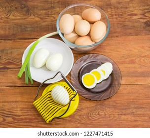 Egg slicer with egg in it, partly sliced, peeled and not cleaned boiled eggs in different dishes on an old rustic table