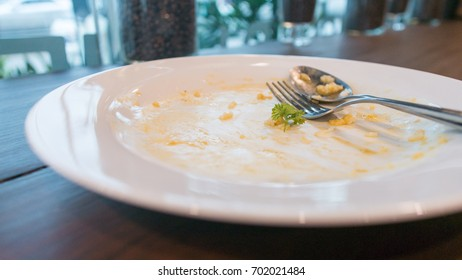 Egg stained plate with fork and spoon on the wooden table background
