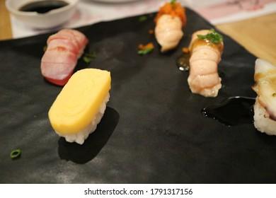 Egg sushi Japanese style on black plate
