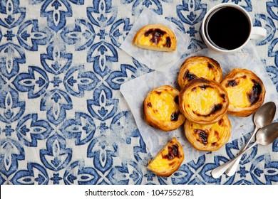 Egg tart, traditional Portuguese dessert, pastel de nata on a parchment paper. Blue textile background. Top view. Copy space.