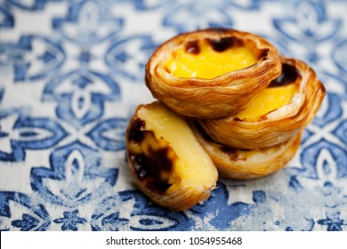 Egg tart, traditional Portuguese dessert, pastel de nata. Blue textile background.