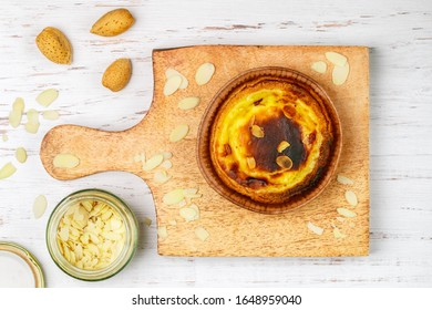 Egg tart, traditional Portuguese dessert, pastel de nata on a wooden cutting Board. Portuguese puff with almond petals. Selective focus