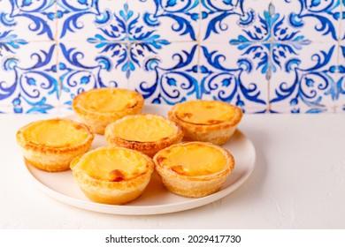 Egg tart, traditional Portuguese dessert, pastel de natapastel de belem. Azulejo tile background.