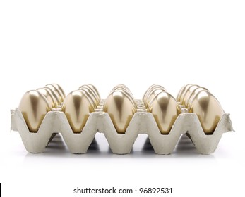 Egg tray filled with golden eggs shot on white background