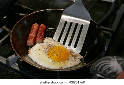 Egg and two sausages with spatula in a frying pan