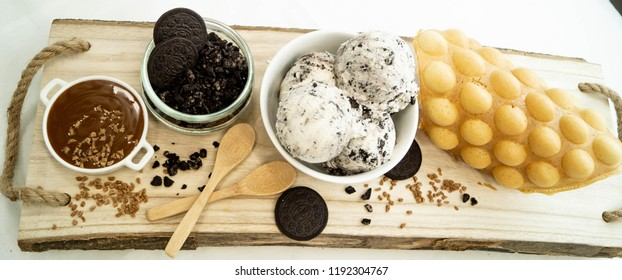 Egg waffle with caramel sauce, oreo cookies and oreo gelato on wooden background