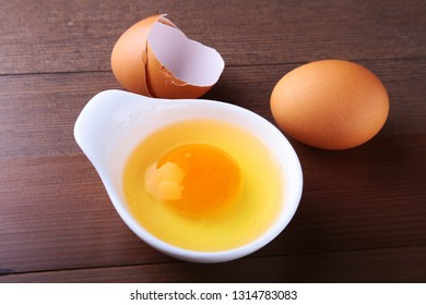 egg yolk in a white bowl and raw egg on the table. ingredients for cooking. concept. View from above.