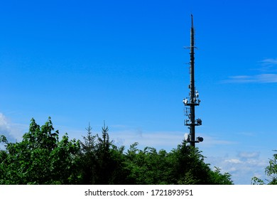 Eggberg transmission tower for radio and television reception. In forest with blue sky.